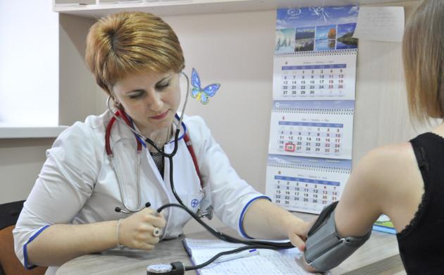 Семейный врач измеряет давление у пациента